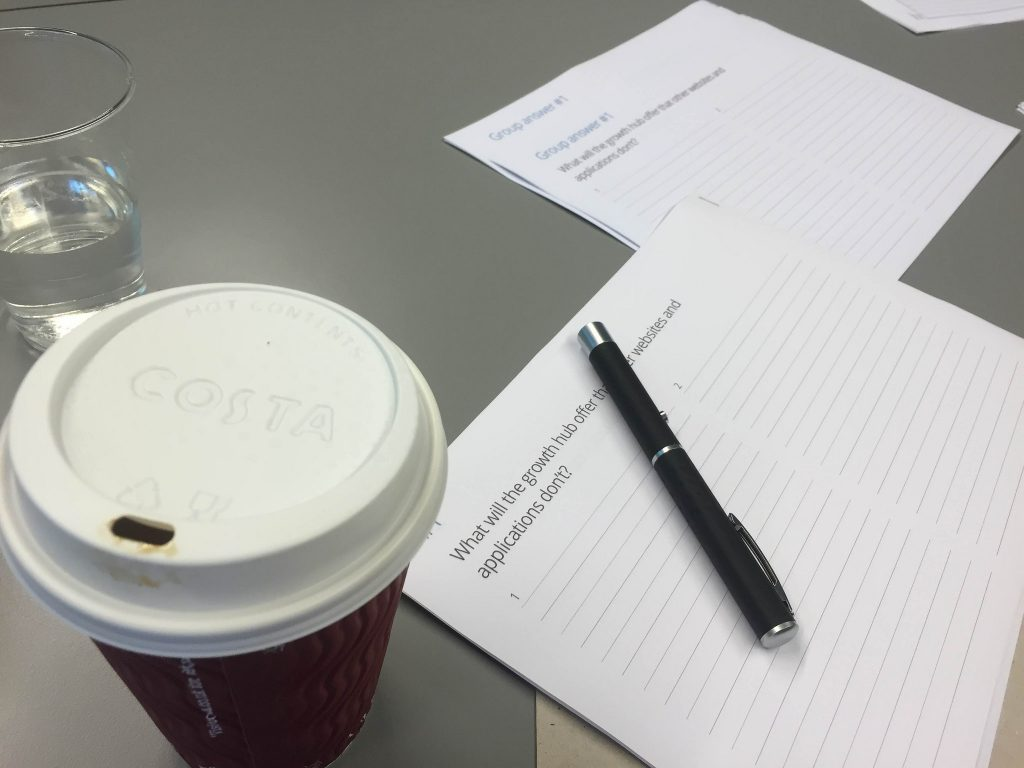 A coffee and some papers scattered on a table at London Growth Hub