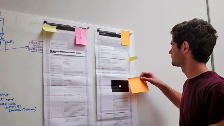 A person sticks post it notes to a wall during a discovery phase application design post it