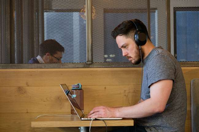A developer works at a desk with headphones on in our London office
