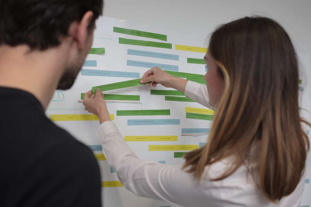 Two people stick feature ideas to a wall as part of a research exercise