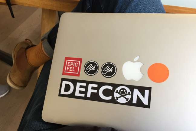 A person displays stickers they have put on their apple laptop
