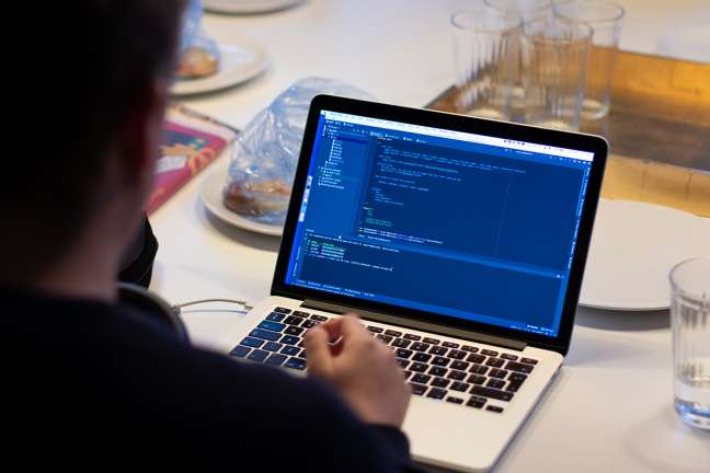 An image of a front-end developer writing code on a laptop computer