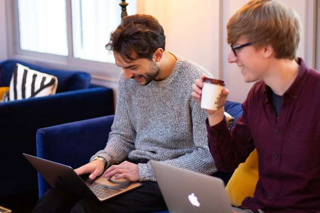Two people work on laptops in a comfortable digital consultancy office in London