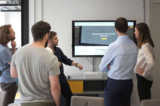 A group of people stand around a screen and discuss the design of a website