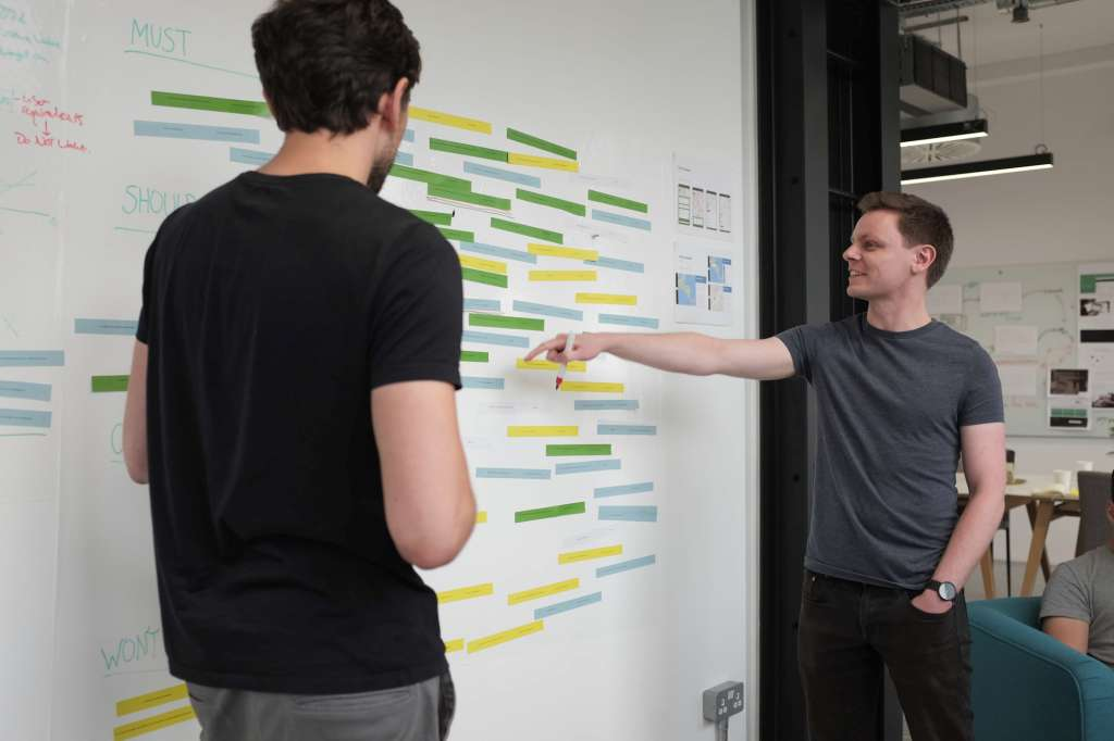 Two people discuss use cases for a web app digital project