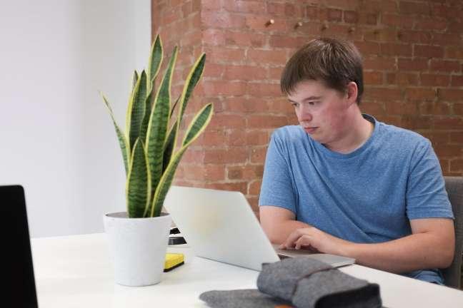 A man in a t shirt works at a laptop at a desk on a digital transformation project