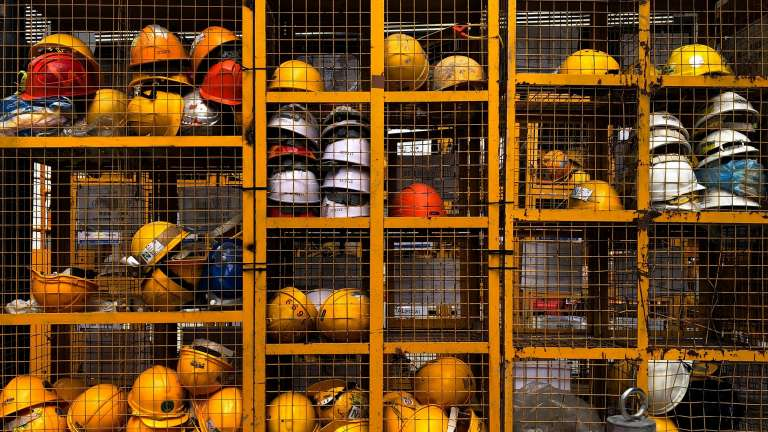 numerous hard construction hats sit on some shelves