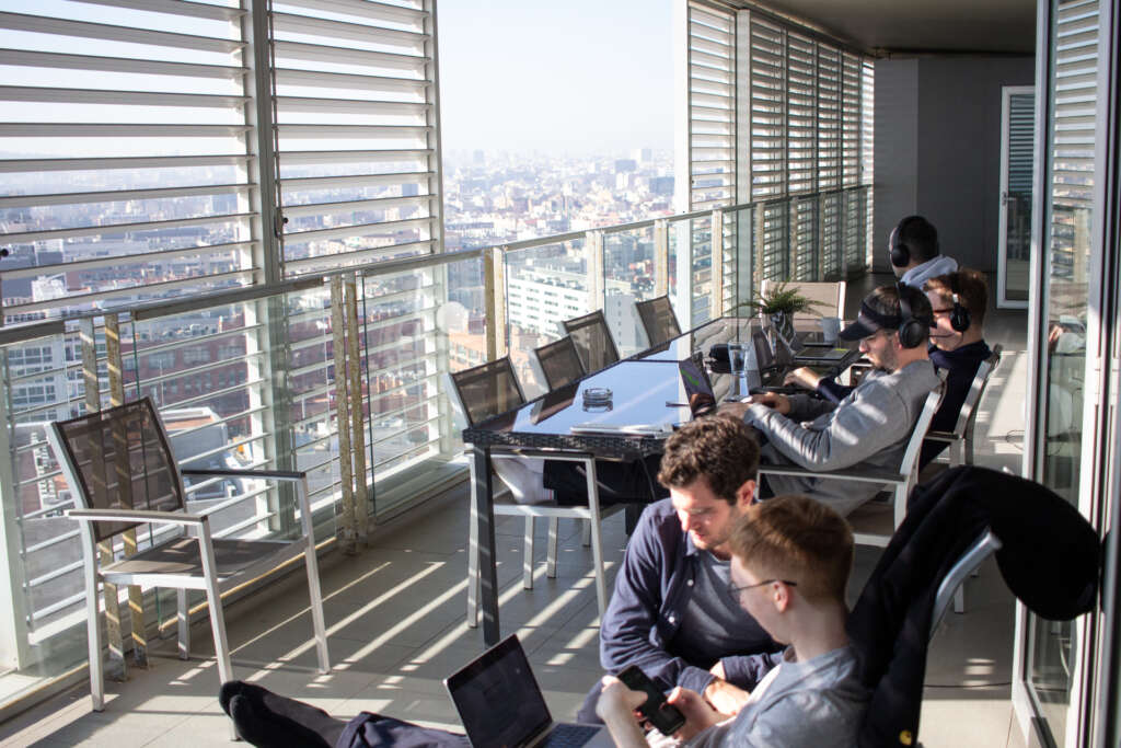 A team at work on laptops on a sunny balcony in Barcelona