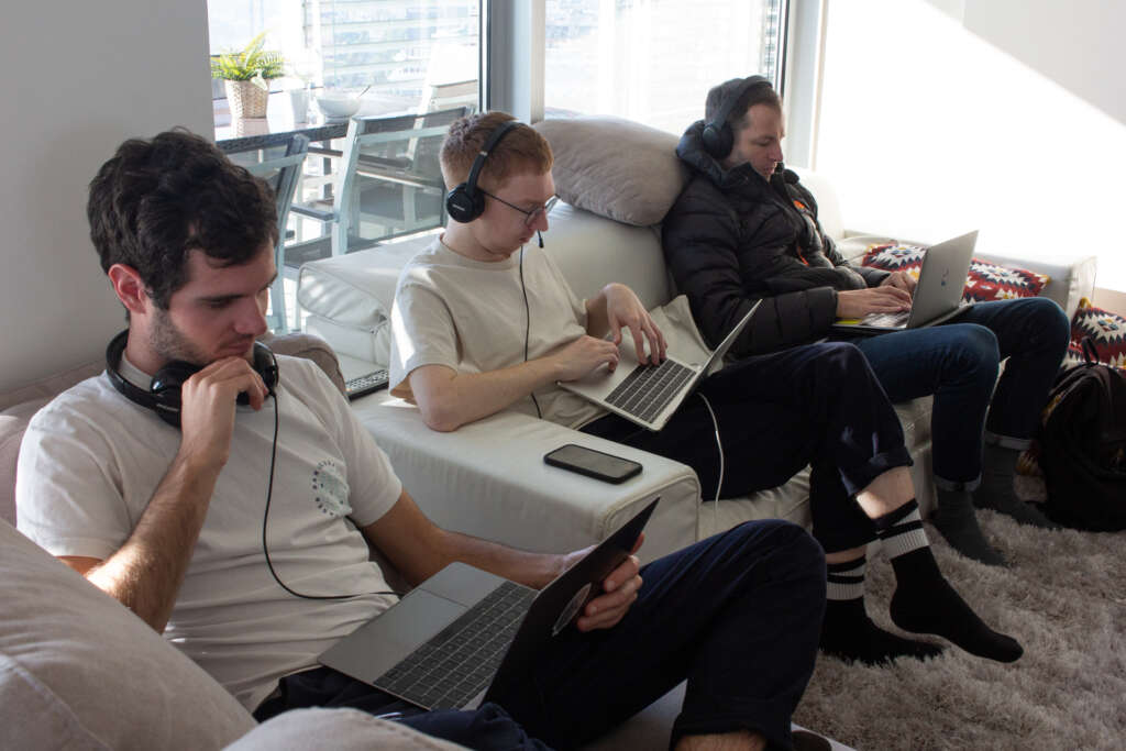 A team of coders work on laptops on a sofa in an apartment.