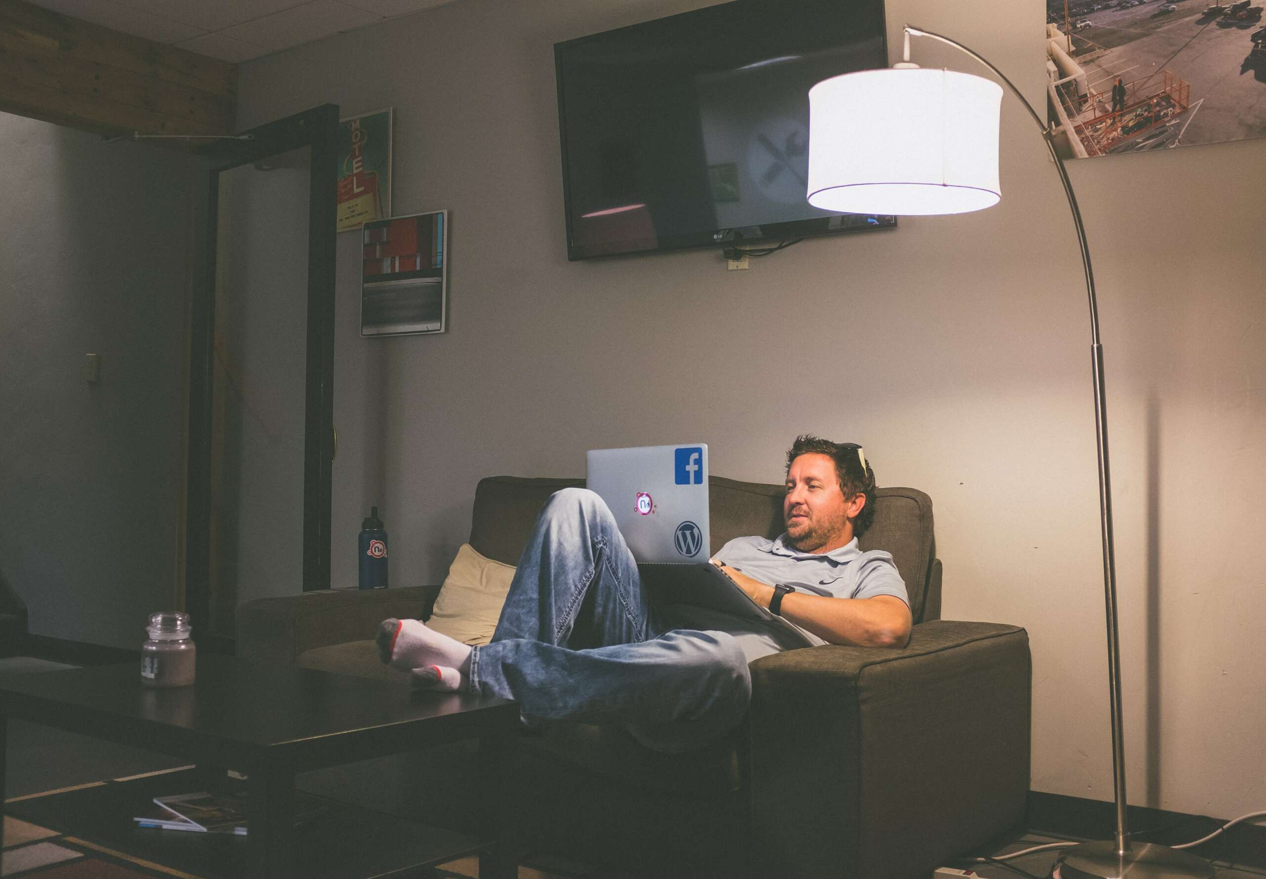 A man works from home on his sofa with a laptop