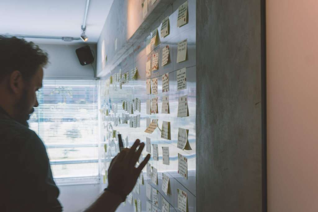 A team examine post it notes on a wall as part of a design sprint 2.0