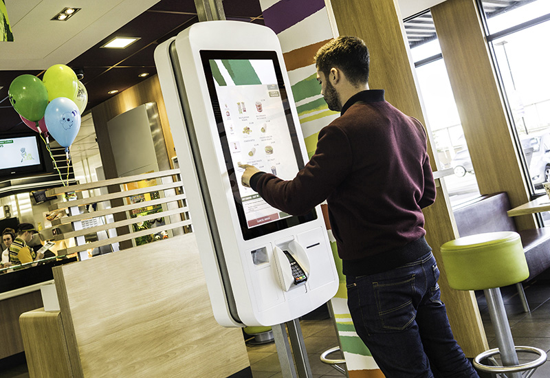 A customer interacts with a McDonalds self serve kiosk