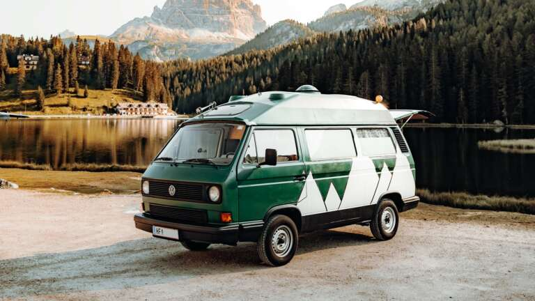 A green camper van parked in a park